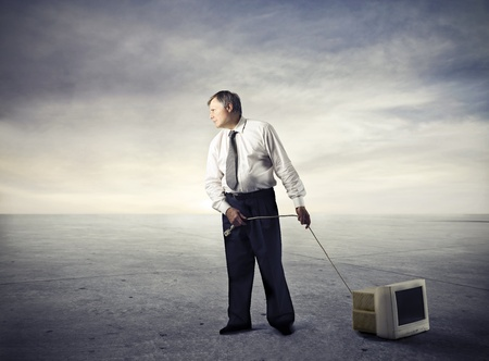 broken computer: businessman drags television in the desert