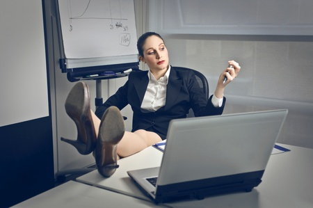 feet on desk: career woman on the phone with feet on the desk