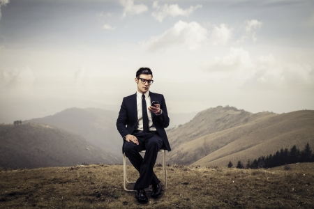 mobile sms: young businessman sitting on the chair in mountain Stock Photo