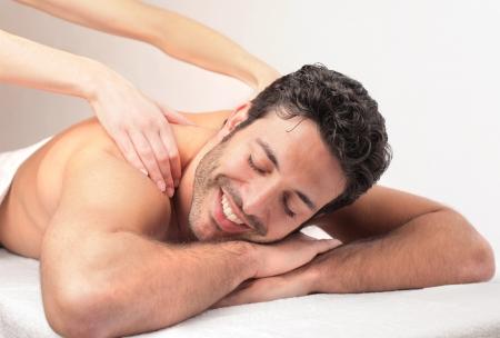 massage homme: bel homme se détend avec un massage