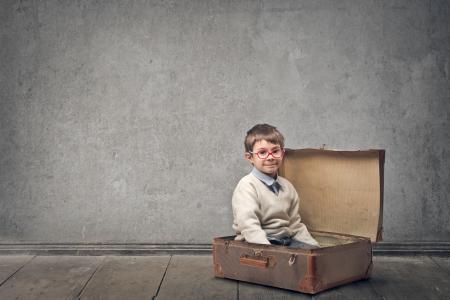 clandestine: little child in a vintage suitcase