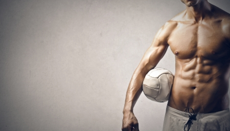 strenght: muscular young man with ball on gray background Stock Photo