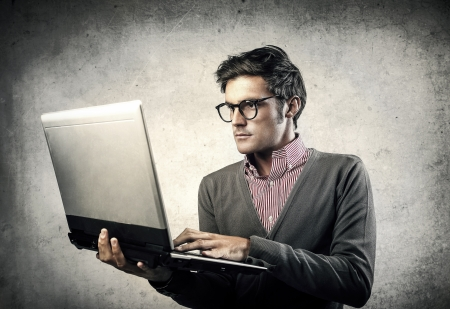 nerd glasses: young businessman working with laptop