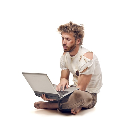 poor people: dirty tramp sitting on the floor with laptop Stock Photo