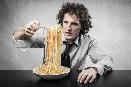 young businessman eating spaghetti photo