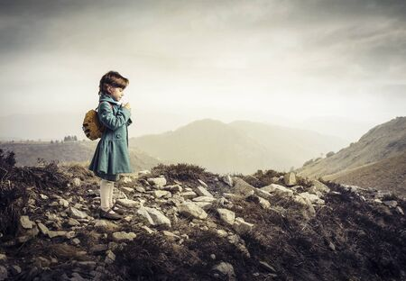 little child with backpack in the mountain photo