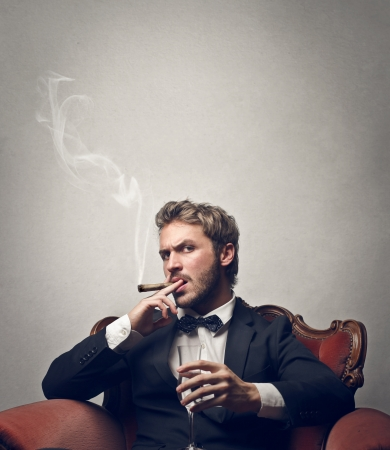 cigar smoke: boss smokes cigar with a glass of champagne Stock Photo