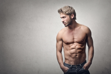 fit on: hombre guapo muscular sobre fondo gris Foto de archivo