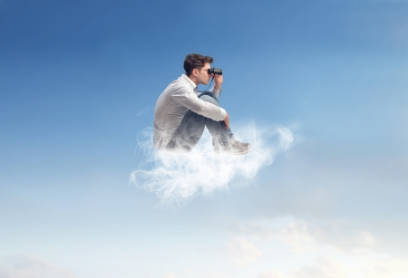 altitude: young man sitting on a cloud in the sky with binoculars Stock Photo