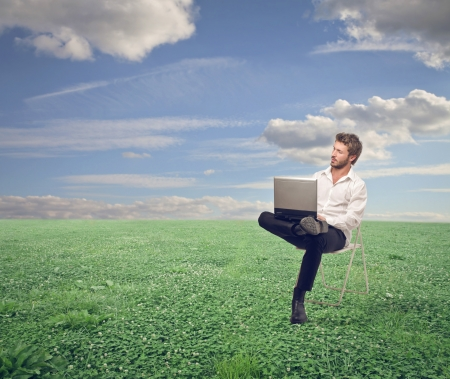 young man sitting on chair with laptop in the country Stock Photo