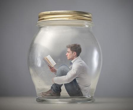 pote: muchacho joven lee el libro sentado en un frasco Foto de archivo