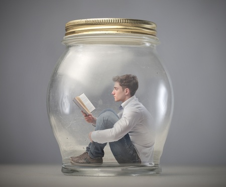 jar: young boy reads book sitting in a jar