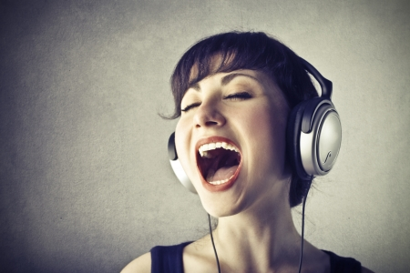 sings: young woman with headphones singing Stock Photo