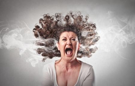 mujer fea: Mujer furiosa gritando con humo saliendo de sus orejas Foto de archivo