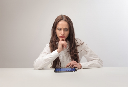 hard to find: doubtful woman using tablet Stock Photo