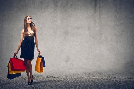 エレガントな女性に灰色の背景に買い物に行く 写真素材
