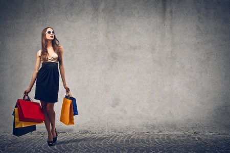 elegante vrouw gaat winkelen op grijze achtergrond