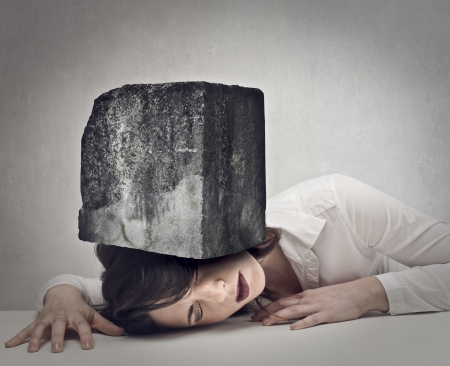 young woman with a big boulder above her head Stock Photo