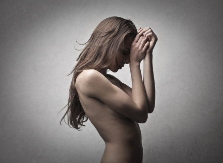 naked woman covers her face