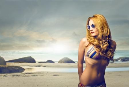 eyewear fashion: young blonde woman in bikini on the beach