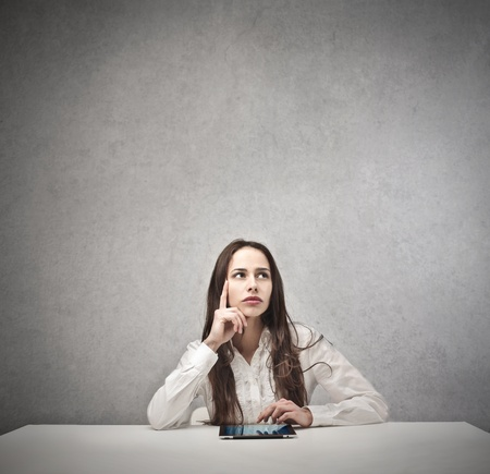 young businesswoman with tablet thinking Stock Photo - 18687771