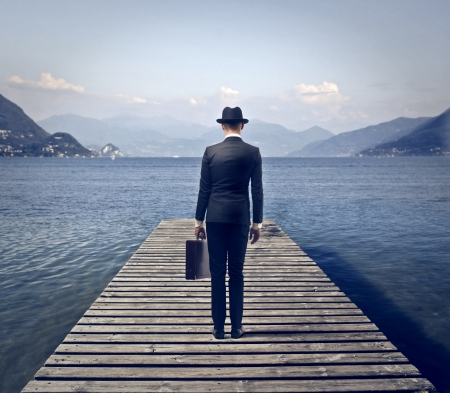 pier: businessman surrounded by the lake and mountains