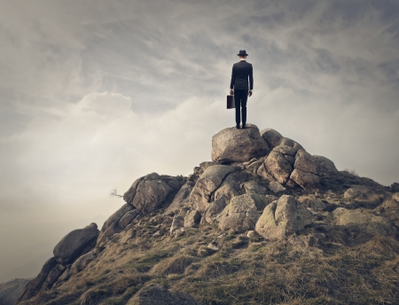 top of mountain: businessman on the top of a mountain
