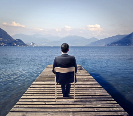 man sitting on a chair surround by the lake and mountains photo
