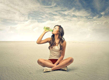 woman sitting and driking from a bottle photo