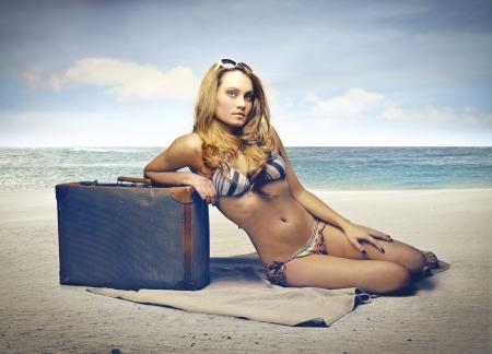 nue plage: femme de d�tente sur la plage avec son suitecase Banque d'images