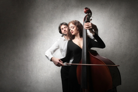 school band: man teaching a woman how to play the double bass Stock Photo