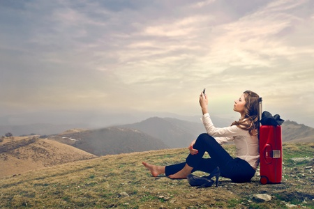 woman on the top of a mountain looking at her mobile photo