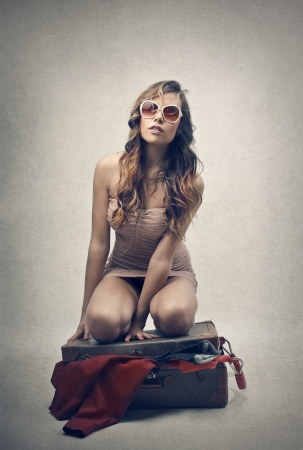 girl trying to close her luggage photo