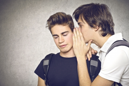 boy telling a secret to an other