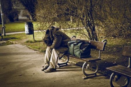 hombre pobre: hombre desesperado que se sienta en un banco con una maleta Foto de archivo