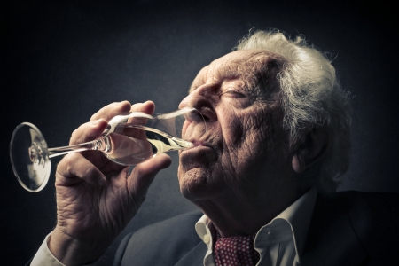 whie: old man driking a glass of champagne