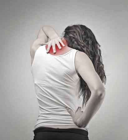 mujeres de espalda: Mujer que toca su cuello rojo Foto de archivo
