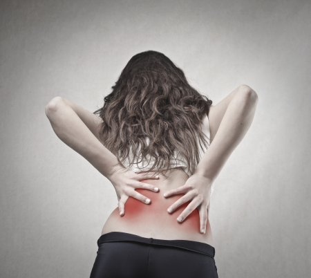 woman back pain: woman holding her back Stock Photo