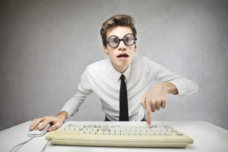 businessman with big glasses looking at a computer
