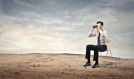 businessman using a binoculars on a chair photo