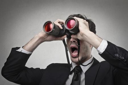 stupor: hombre de negocios en busca de algo con binoculares Foto de archivo