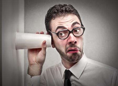 oir: hombre tratando de escuchar con un vaso Foto de archivo