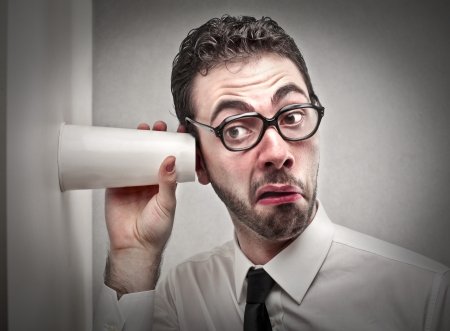 gossip: man probeert te luisteren met een glas Stockfoto