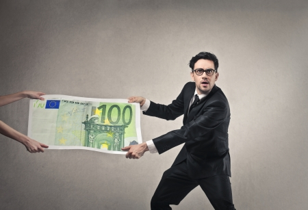 repayment: businessman pulling to himself 100 euros Stock Photo