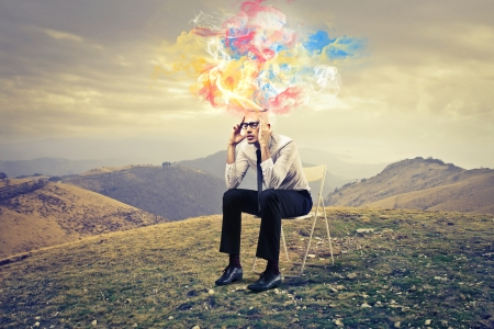 man sitting on a chair with ideas coming out from his head photo
