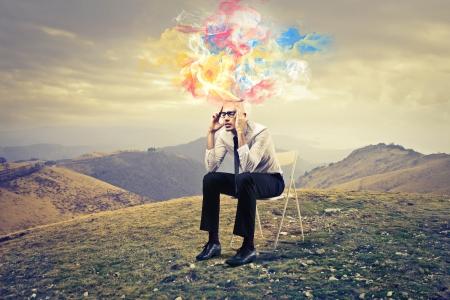 Mann sitzt auf einem Stuhl mit Ideen, die sich aus dem Kopf Standard-Bild
