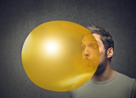 man blowing a yellow balloon Stock Photo - 19687602