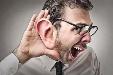 hombre tratando de escuchar con una enorme oreja
