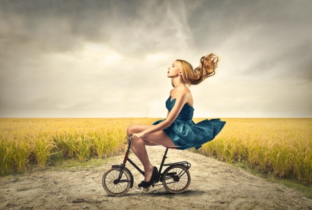 woman riding a little bike in the countryside Stock Photo