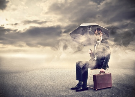 lonliness: businessman wearing a gas mask under and umbrella